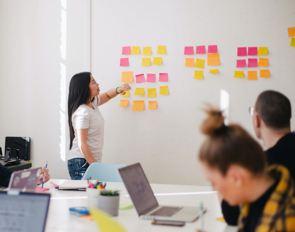 Woman pointing to whiteboard during Business English