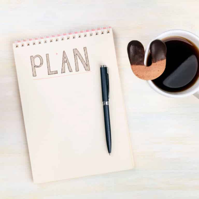 Lucky plan. An overhead photo of a spiral notebook with the handwritten word Plan, with a cup of coffee with a lucky horseshoe shaped cookie, on a desk with copy space